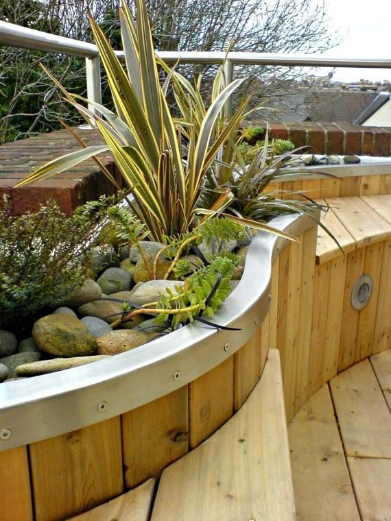 A curved bed on a roof balcony with stainless steel trim